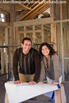 Picture of a happy ethnic couple leaning on a set of blue prints atop a saw horse in the new home being built.